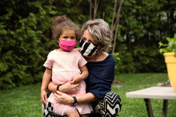 Grandmother and daughter wearing face masks together outside.