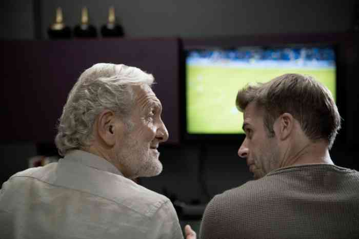 Grandfather and grandson watching a football match on tv