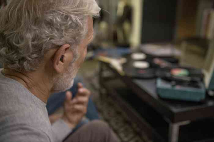 man listening to music wearing a hearing aid