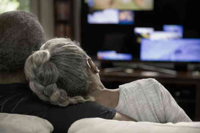 An elderly couple with BTE hearing aid watches TV on a sofa