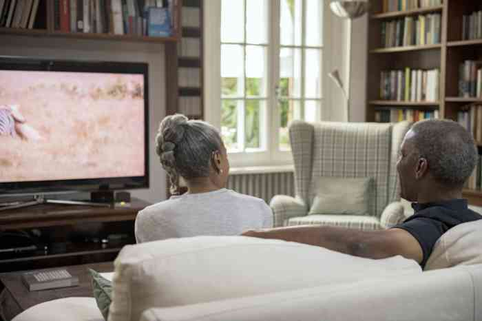 Couple with hearing aids watching TV on a sofa