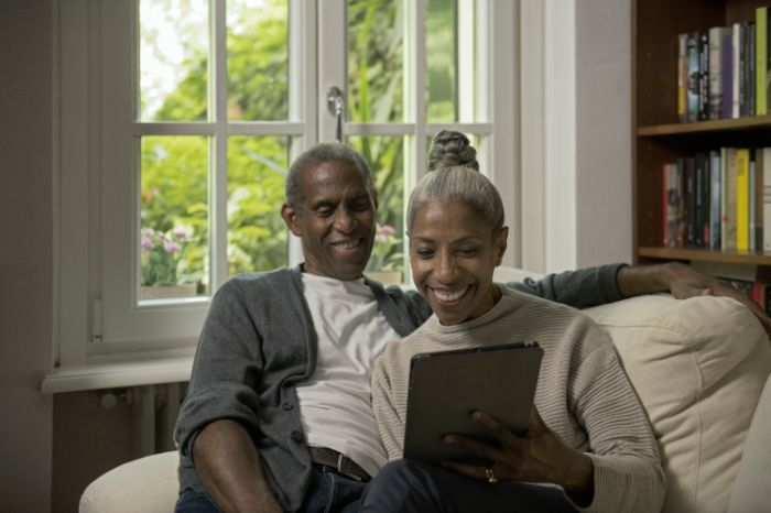 Elderly couple with invisible hearing aids making a call with their tablet