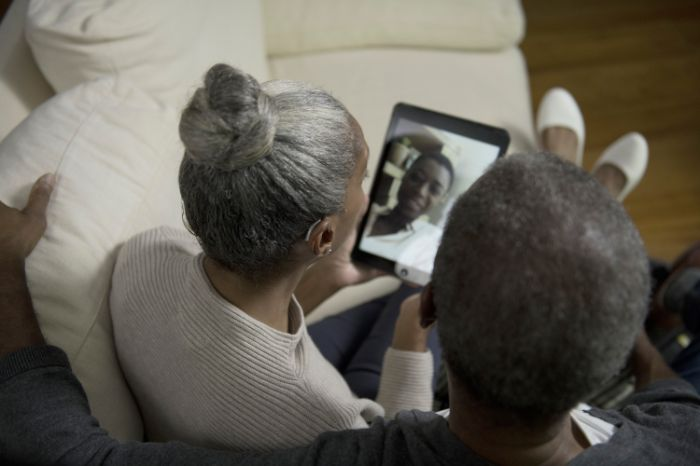 Elderly man and woman with hearing aid making a videocall with their tablet