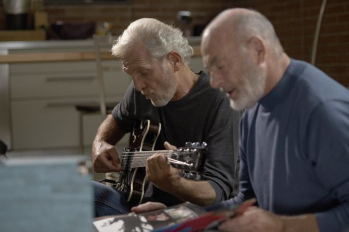 Two elderly friends playing guitar and singing together