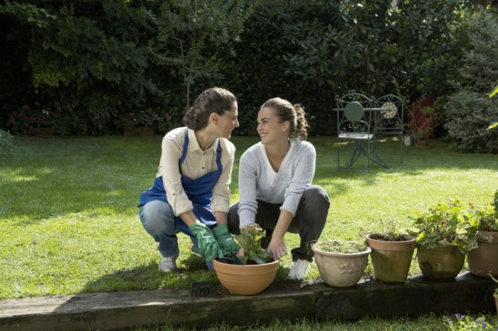 Mother with invisible hearing aid and her daughter gardening