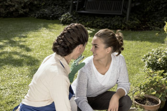 A woman with BTE hearing aid and her daughter gardening