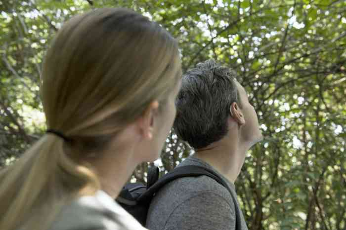 Profiles of a woman and a man with hearing aids in the woods