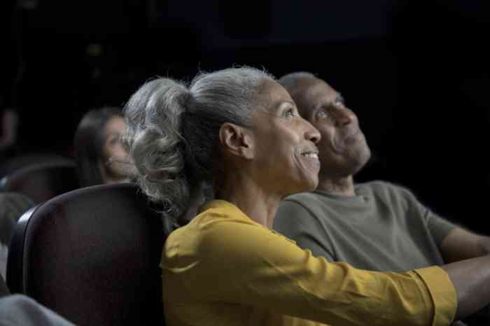 Couple with invisible hearing aids watching a movie at the cinema