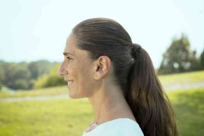 Profile of a woman with invisible hearing aid in a park