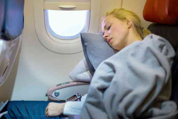 A young girl sleeping during a flight