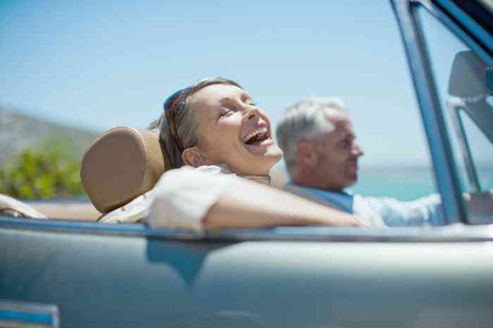 Elderly couple in a convertible car with sea in the background