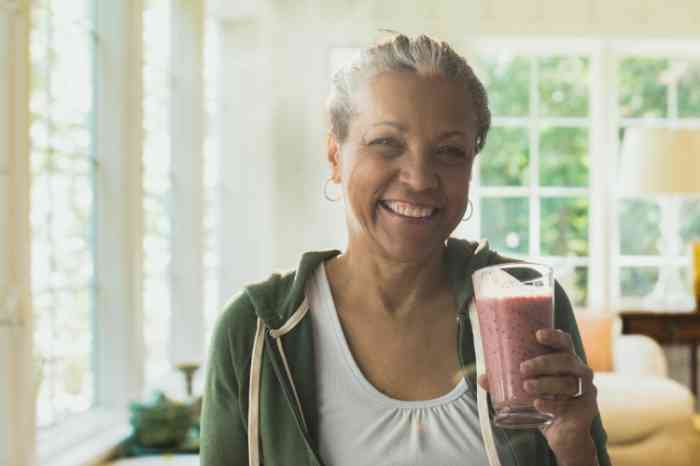A woman smiling with a milkshake in her hand