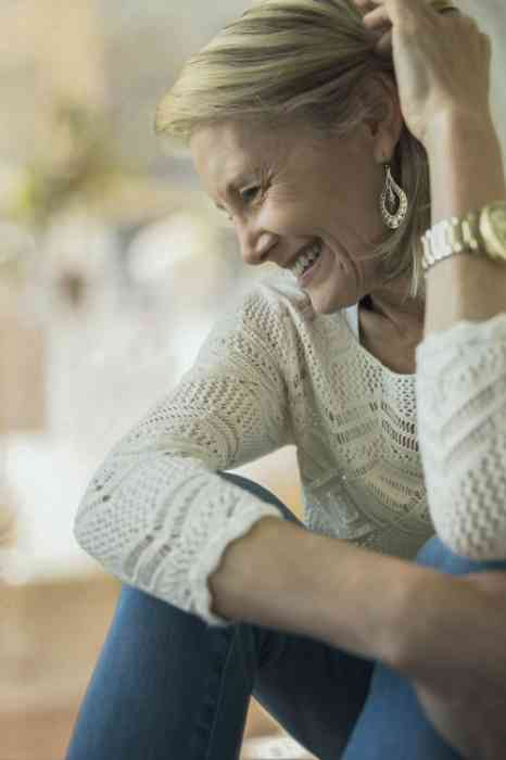 Smiling woman with invisible hearing aids