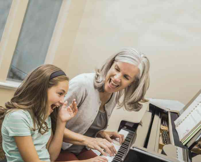 Elderly woman playing a piano with her granddaughter
