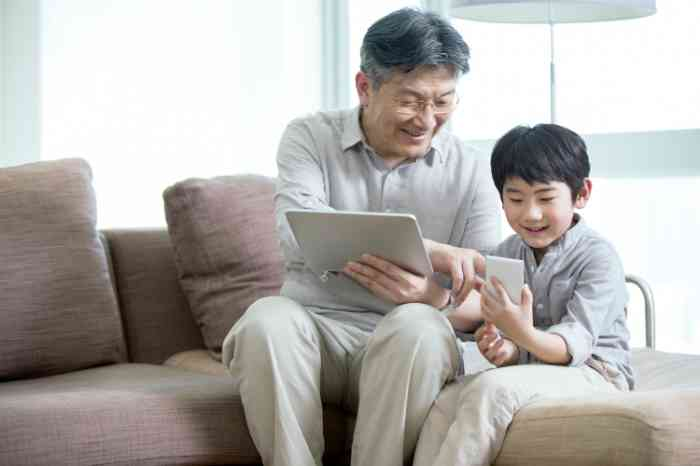 Elderly man with a tablet helping his son with a smartphone