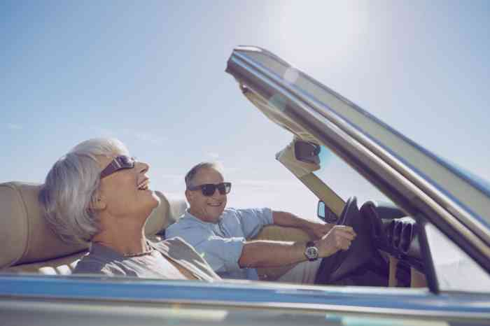 Elderly couple driving a convertible car enjoying a sunny day