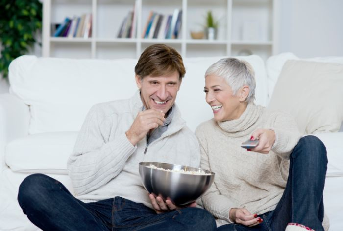 A girl and a man with BTE hearing aid watching TV eating pop corns