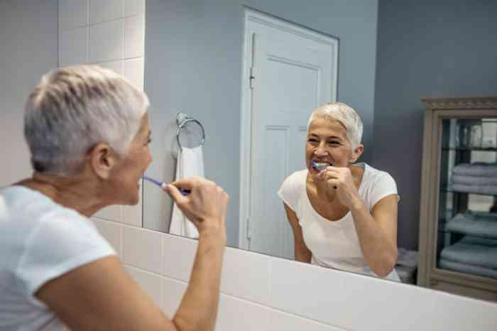 Woman in a bathroom washing her teeth
