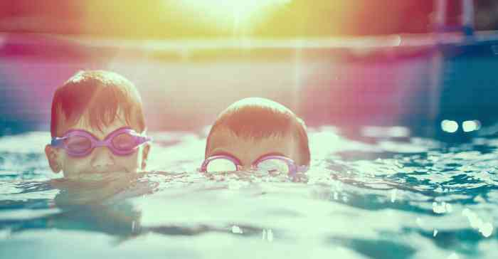 Two children with swimming goggles in a pool
