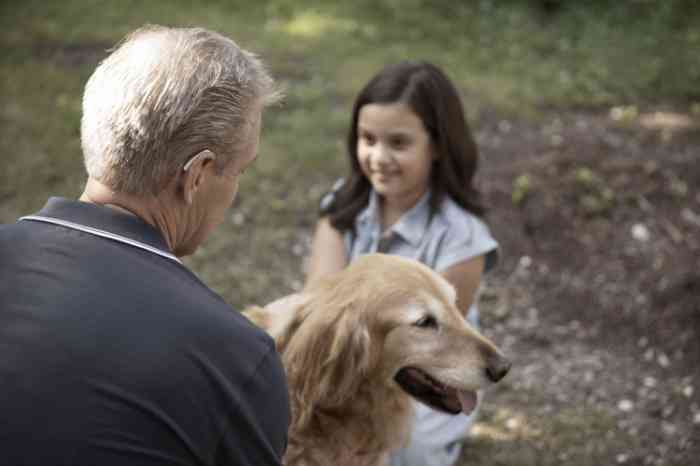 man wearing a hearing aid with dog and granddaughter