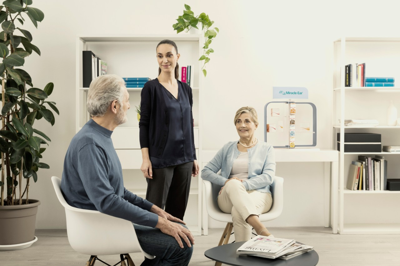 One of our hearing aid experts talking to two customers in a Miracle-Ear center