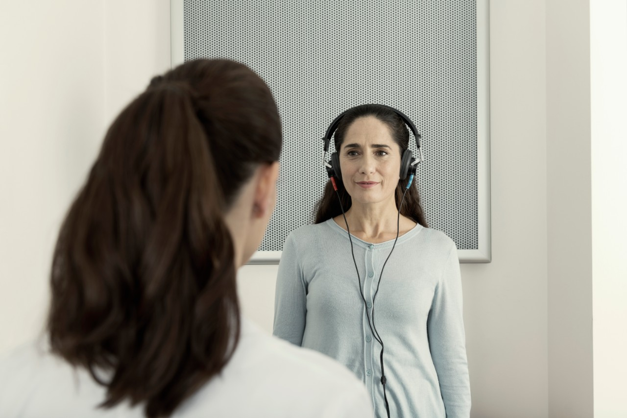 Miracle-Ear audiologist and a woman with headphones during a hearing test