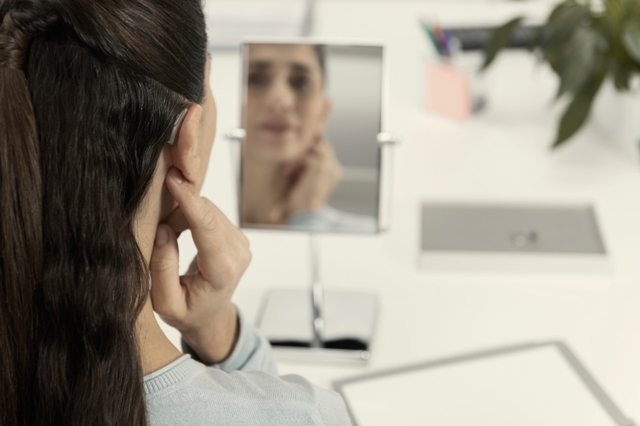 Woman with BTE hearing aid looking herself at the mirror