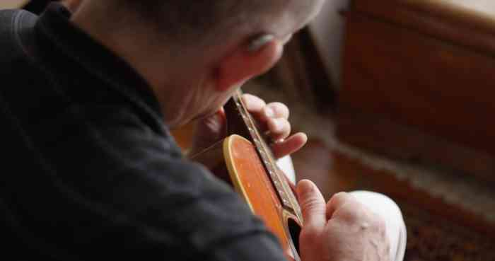 Man with BTE hearing aid playing guitar
